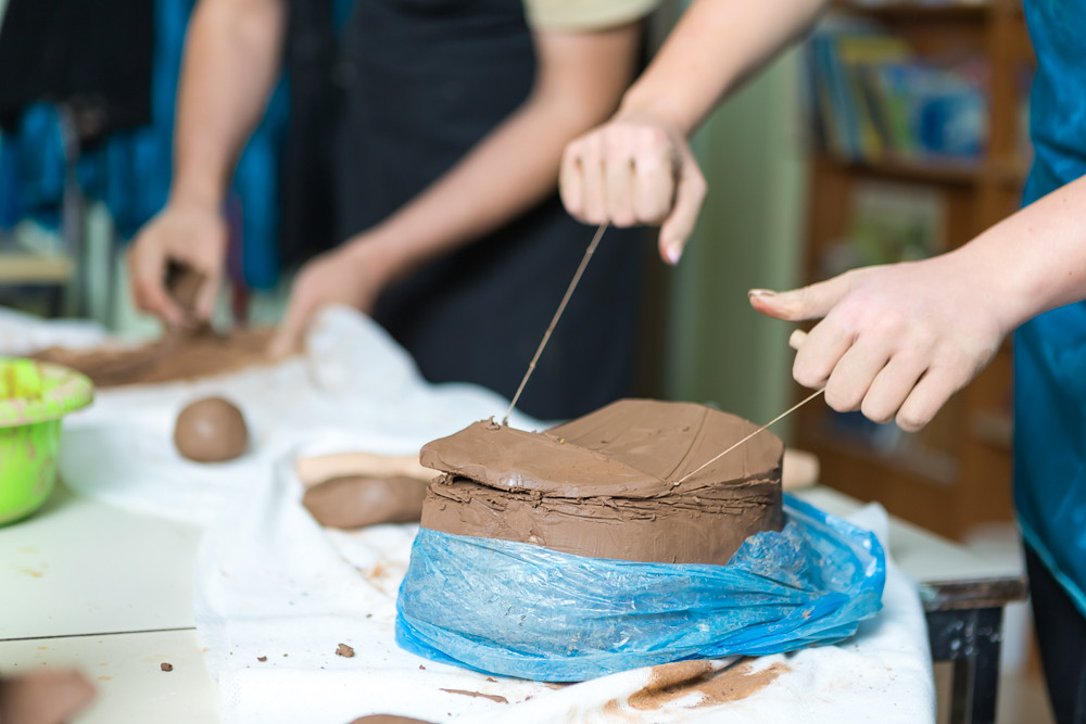 Pottering Concept. Hands of Professional Ceramists During a Process of Clay Preparation With Wires on Table in Workshop.