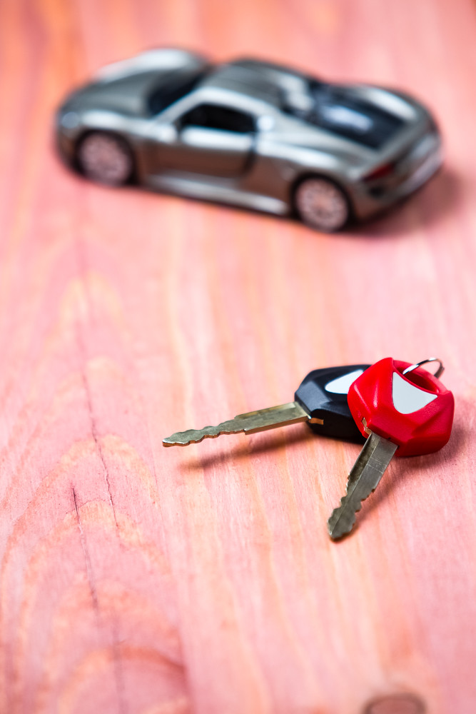 Car Loands and Credit Concepts. Car Symbol Along With bunch of Keys Against Vintage Wooden Background.