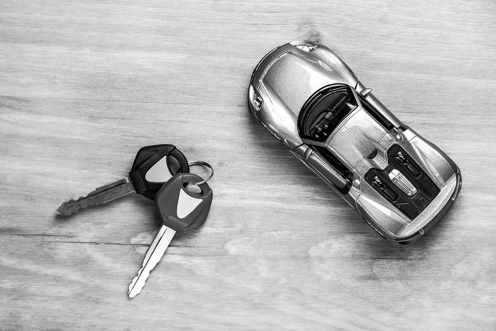 Car Loands and Credit Concepts. Car Symbol Along With bunch of Keys Against Vintage Wooden Background. Black and White Image.