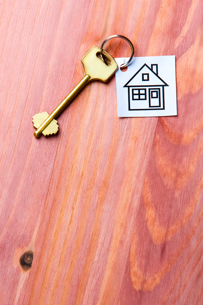 Family and Home Concepts. House Symbol Along With Golden Key Over Vintage Wooden Background.