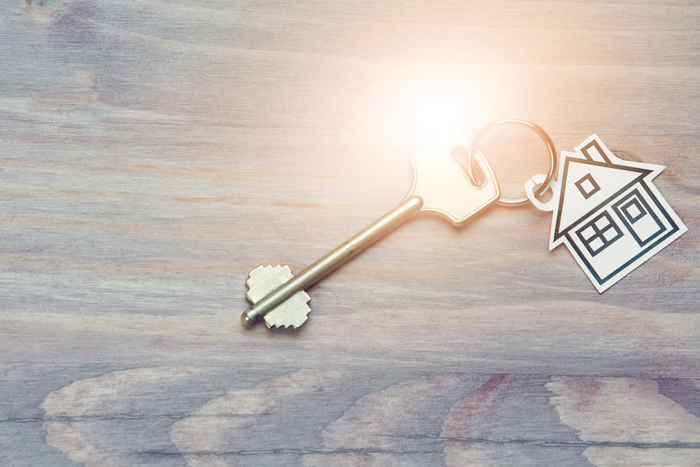 Family and Home Concepts. Home or House Symbol Along With Golden Key Over Vintage Wooden Background. Sunflare Added.