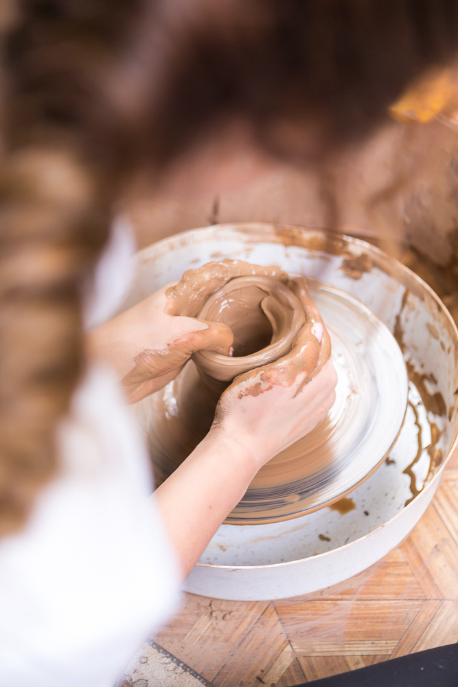 Clay Making Concepts. Closeup of Female Worker Hands Preparing a Piece of Clay on Potters Wheel in Workshop.