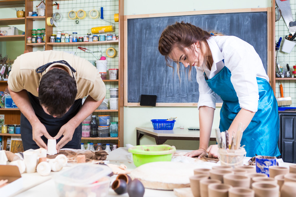Claymaking Process Concept. Two Professional Ceramists During a Process of Clay Preparation on Tables in Workshop.