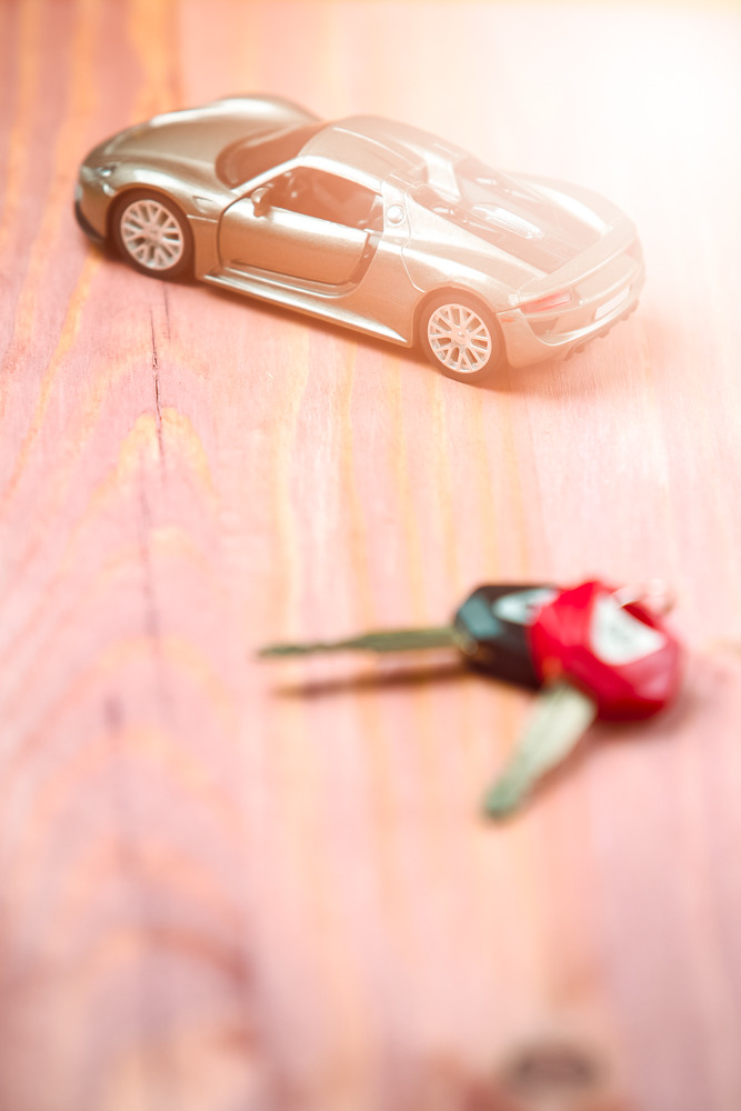 Car Loands and Credit Concepts. Car Symbol Along With bunch of Keys Against Vintage Wooden Background. Sunflare Added