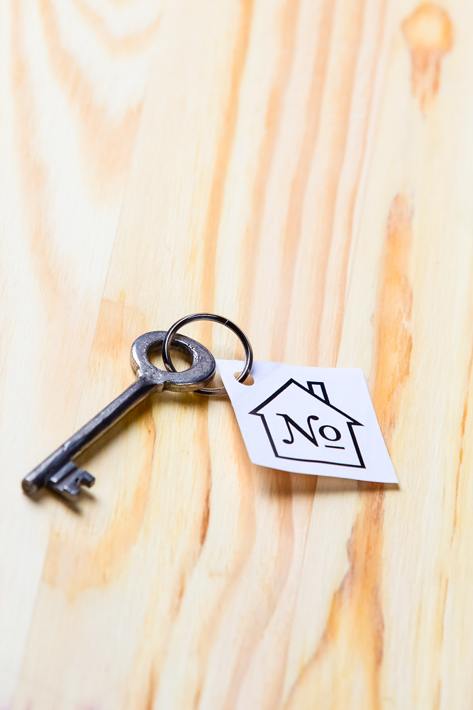 Home Concepts. Home or House Symbol Along With Old Silver Key With Number Mark Over Vintage Wooden Background.