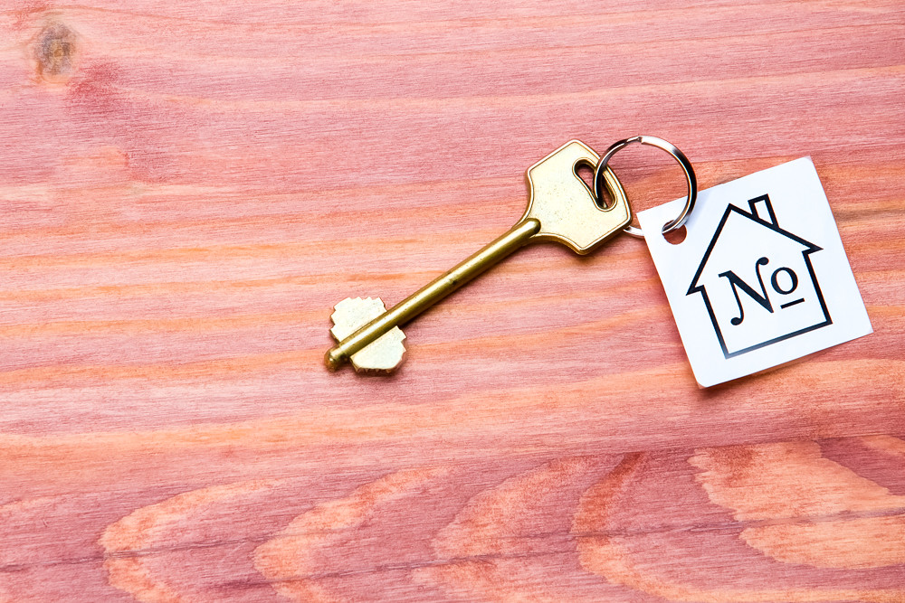 Family and Home Concepts. Home or House Symbol With Number Mark Along With Golden Key Over Vintage Wooden Background.