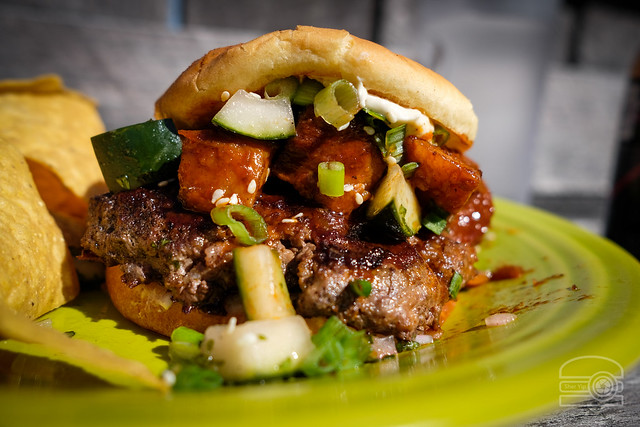 "The ""Red, Red Swine"" Burger - toasted potato bun, Szechuan cream cheese, sweet and tangy cucumber salad, sweet and spicy pork belly, green onions and sesame seeds  - Black Bear Burritos Evansdale"
