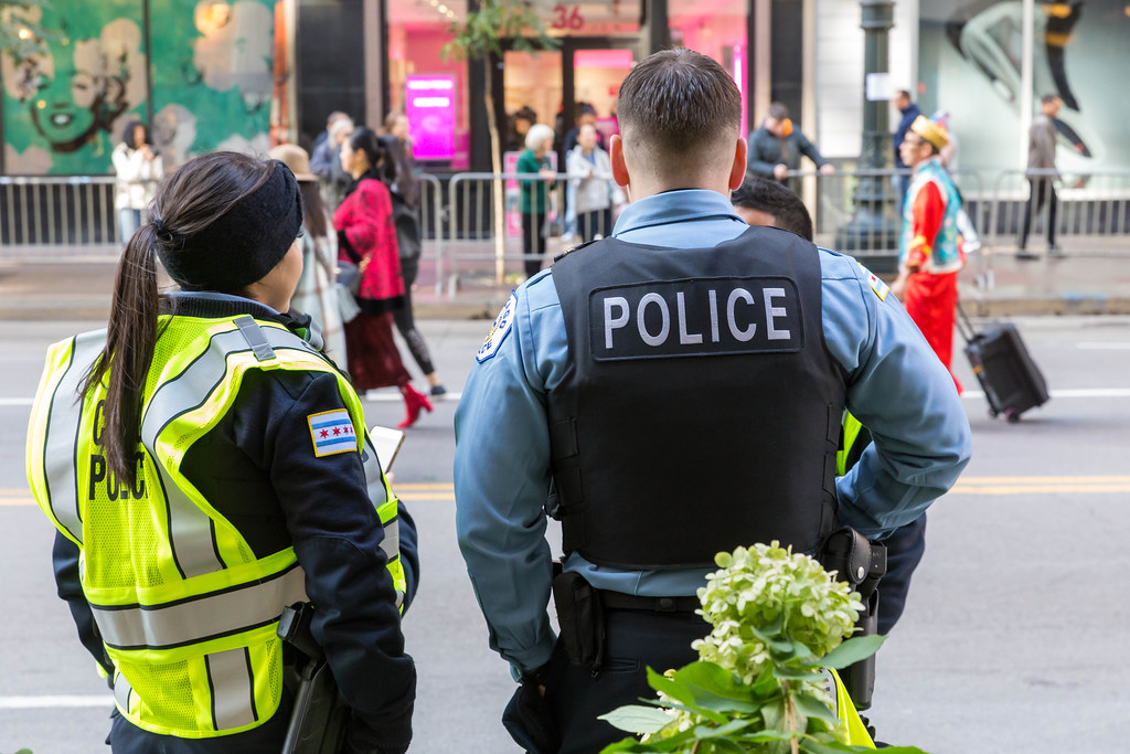 A female and a male police officer seen from behind on the streets of Chicago during the Columbus Day Parade