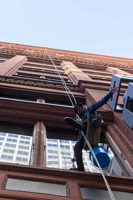 Gebäudereiniger grüßt den Fotografen während der Arbeit am Seil ohne Gerüst