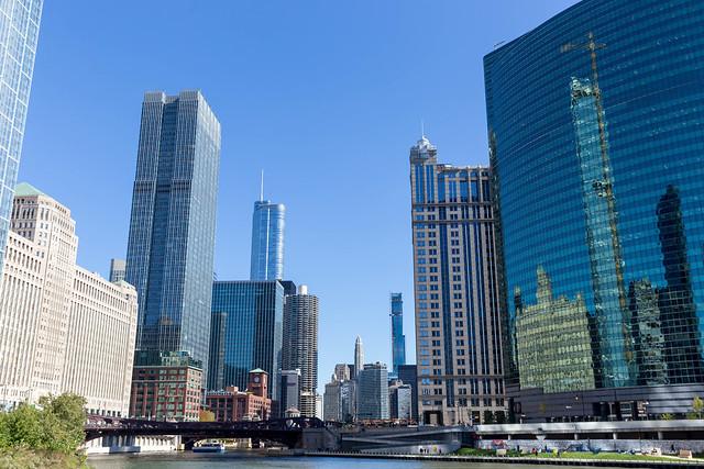 Die gekrümmten Glasfassade des Nuveen Gebäudes am Chicago River mit Spiegelung von anderen Wolkenkratzern