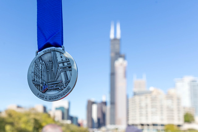 Close-up of the Chicago Marathon Medal with the Willis Tower, the 311 South Wacker Drive and the River City in the background on a sunny day