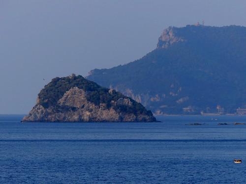 Vista verso l'isola di Bergeggi e alle sue spalle Capo Noli. Partenza dal Porto di Vado Ligure (Savona, Italia). Corse 2019.