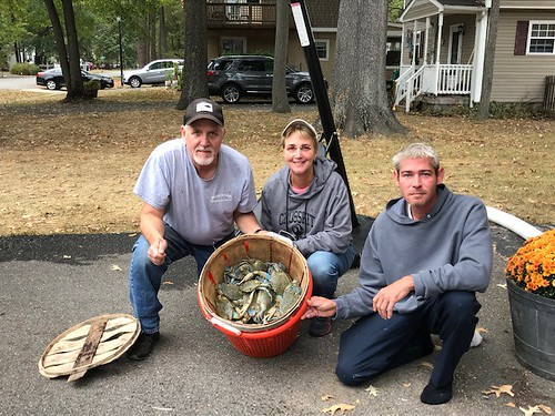 Photo of three people holding a basket full of blue crabs