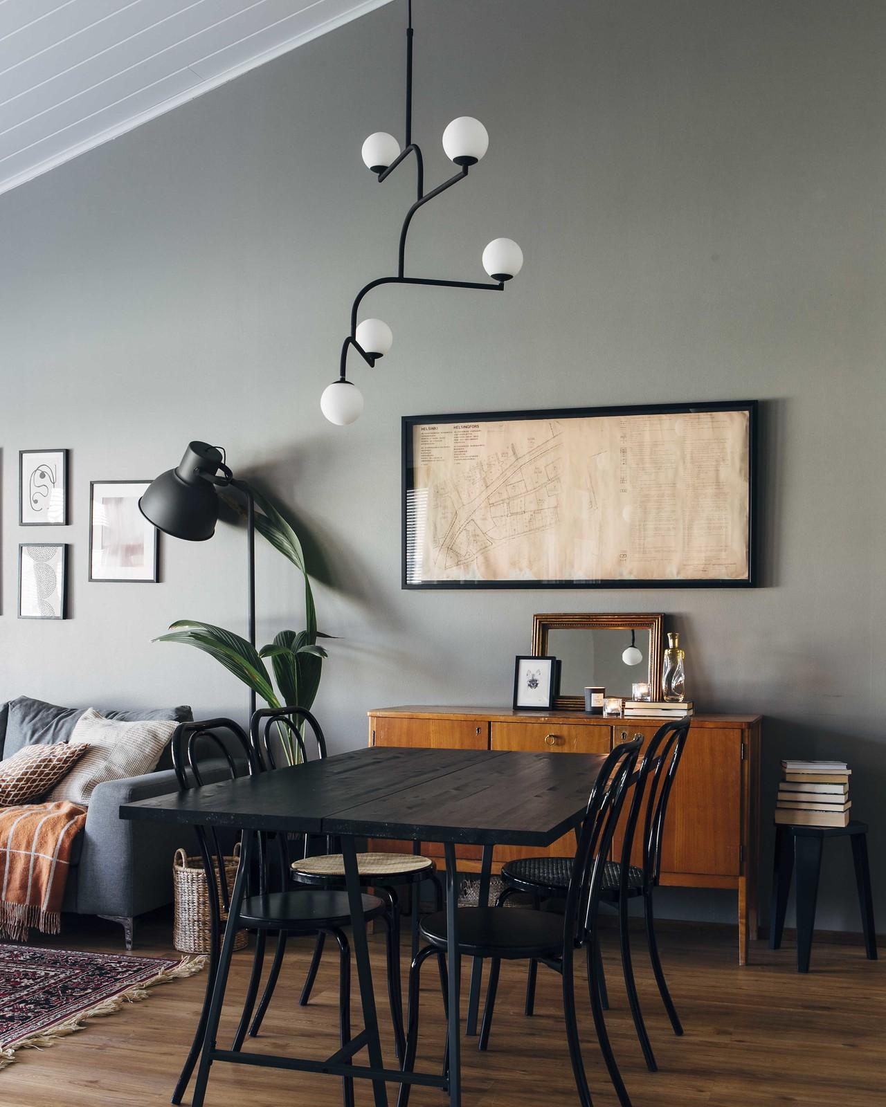 Ruokailutila, jossa musta pöytä ja mustat wieniläistyyliset tuolit. Pöydän takana on vintage senkki.