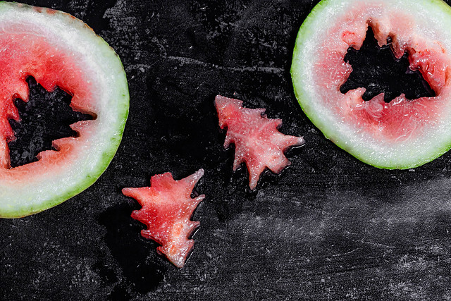 Pieces of watermelon in the shape of a Christmas tree on a black background
