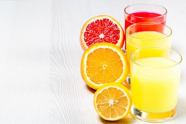 Orange, lemon and grapefruit fresh juices on a white wooden background