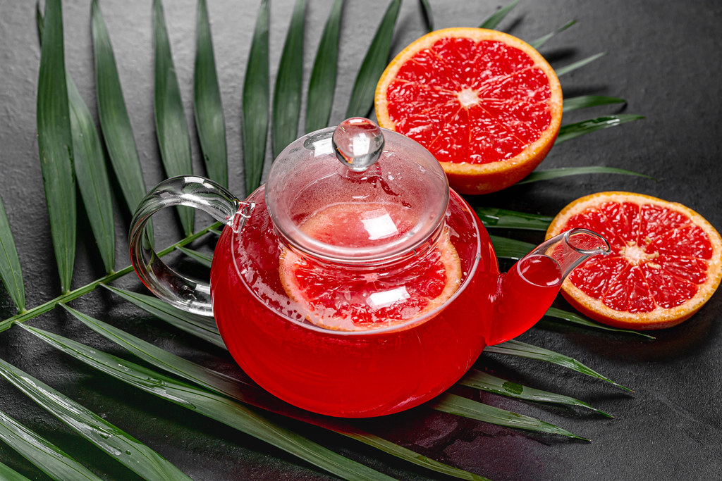 Hot tea with slices of fresh grapefruit on black background with green leaf