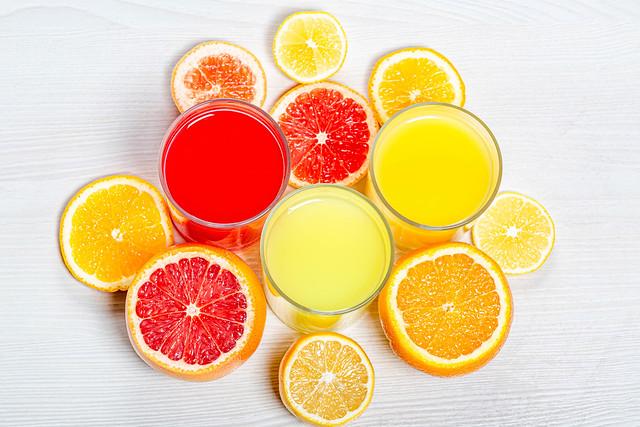 Top view orange, lemon and grapefruit juices with slices of fresh citrus
