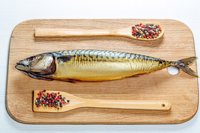 Whole smoked mackerel on a wooden kitchen Board with a mix of peppers. Top view