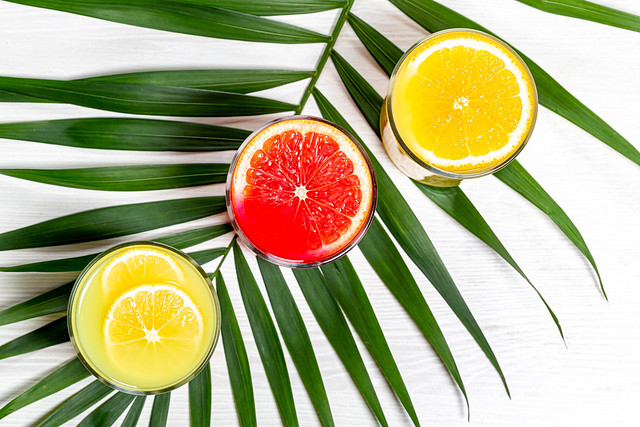 Top view glasses with lemon, orange and grapefruit juice with green leaf