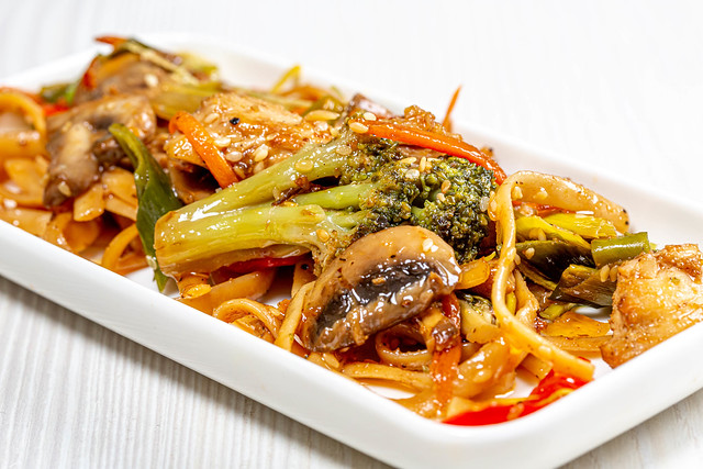 Close-up of noodles with sauce, vegetables and sesame seeds