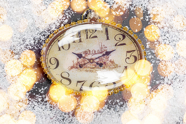 The concept of approaching the New Year. The clock on the snow and bokeh