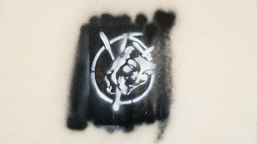 Graffiti Guy Fawkes mask on building wall