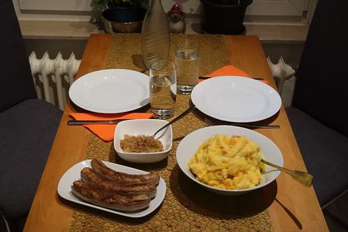 Wildschwein-Bratwurst mit Zwiebelsoße zu Kürbis-Kartoffelstampf (Tischbild)