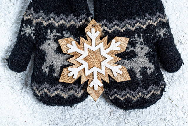 Children's hands in mittens hold a wooden snowflake on a background of snow. Winter concept