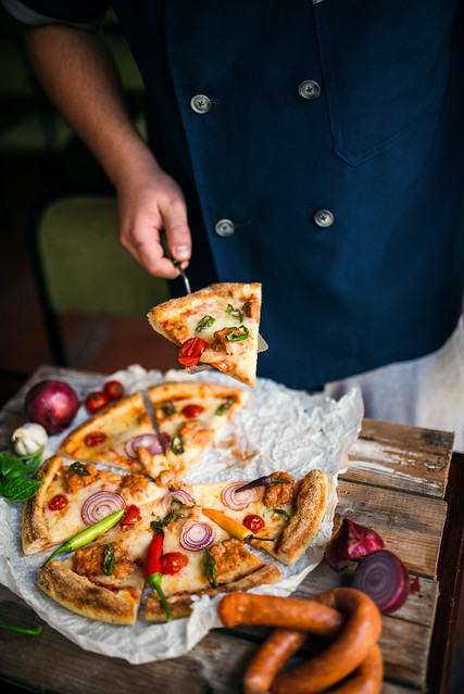 A chef in an uniform serveing a slice of pizza at a restaurant