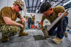 Sailors assigned to Naval Mobile Construction Battalion (NMCB) 5 and airmen assigned to 554th Red Horse Squadron work together to build a latrine facility on the U-Tapao Royal Thai Navy airfield base, Oct. 17. (U.S. Navy/MC1 Julio Rivera)
