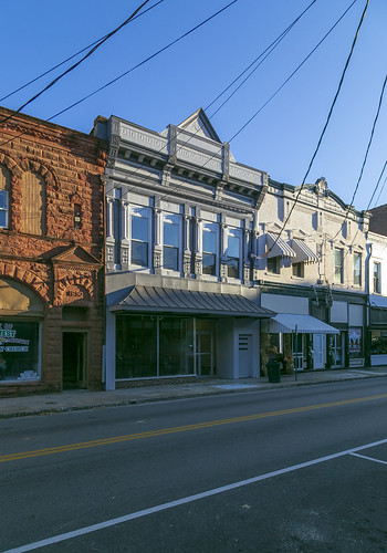 building structure historic commercial twostory ornate prefabricated metal facade 11windows storefront awning sidewalk street cables wires cornice brackets pilasters colonettes corbels cynthiana kentucky harrisoncounty