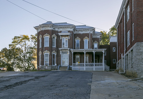 house dwelling residence historic twostory brick ornate italianate polygonalbay cornice brackets 11windows keystones porch steps friezewindows slope parkinglot cables wires trees cynthiana kentucky harrisoncounty cook