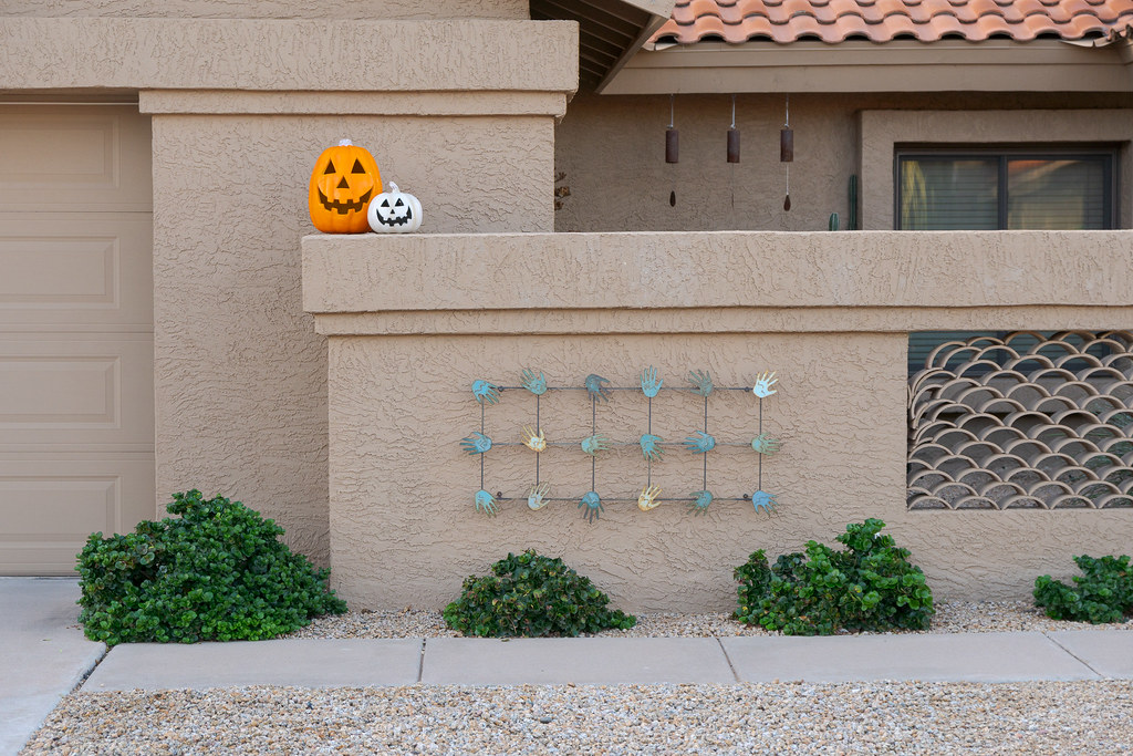 An orange and a white pumpkin sit above artwork full of hands on a house in the Buenavante neighborhood of Scottsdale, Arizona