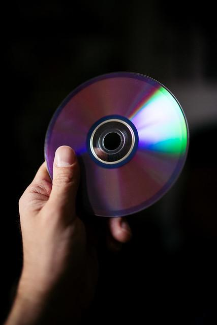 A hand holding an old compact disc as optical media is nearing its end of life