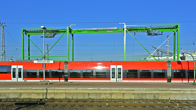 Colours encounter: The green gate passed by a red train.
