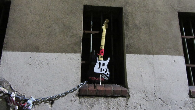 Art Pieces Spotted Toy Guitar And A Tiger Cuddly Toy protruding From Windows Of A Building In A Lane In Glasgow Scotland - 1 Of 2