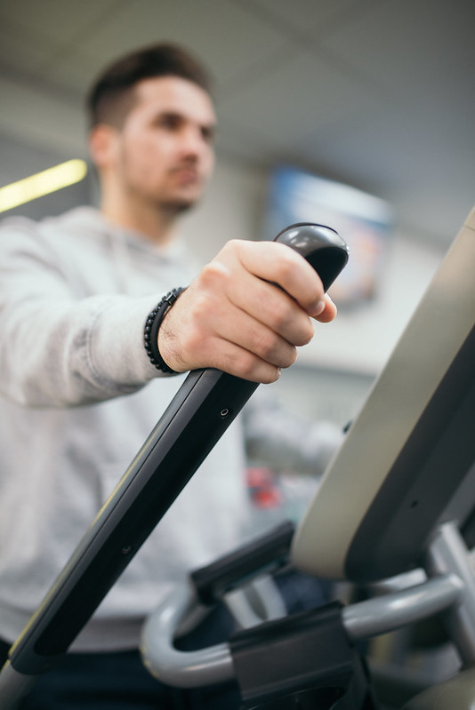 Young attractive man practicing on exercise bike during cross training in a gym