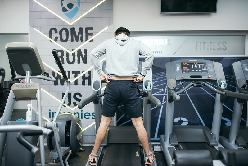 Young man running on treadmill during sports training in a gym