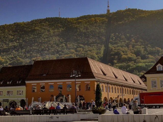 Sunny afternoon in the city center of Brasov, Romania with the Carpathian mountain background.