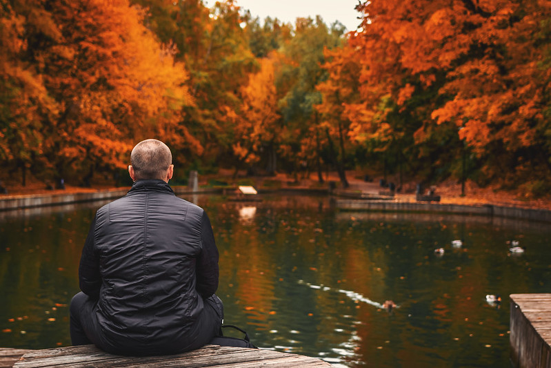 Alone man sits beside a pond in the park. Autumn background.