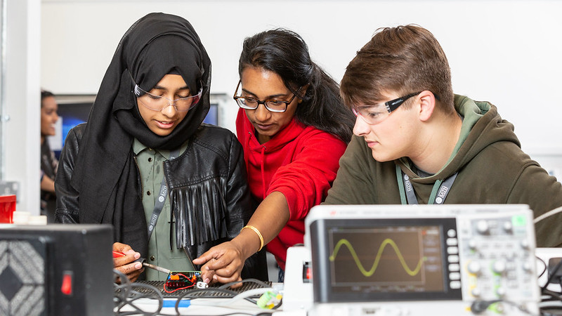 Two students working on a circuit board with a Student Ambassador who is wearing a red hoody