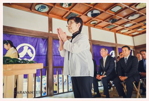 地域の神社のお祭り 祭殿に向かって手を合わせる人