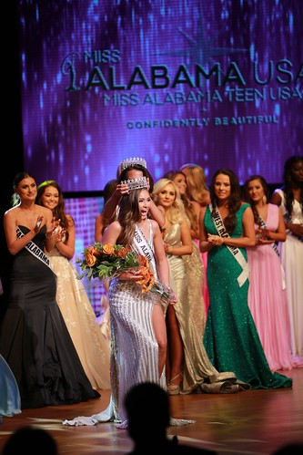 Former Miss Alabama USA crowns Kelly Hutchinson as the new Miss Alabama USA while other contestants look on.