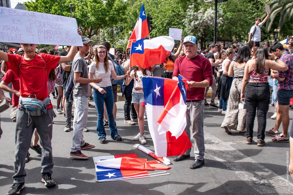 Продавец флагов на протестах в Сантьяго.