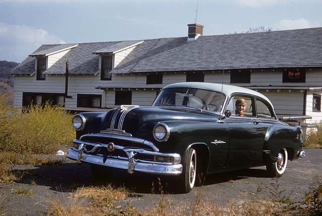 Mom takes a spin in dad's new 1953 Pontiac Chieftan in the weedy parking lot of an old restaurant somewhere in Connecticut. Love those wide whitewall tires, the enormous amount of chrome and painted hub caps. October 1954
