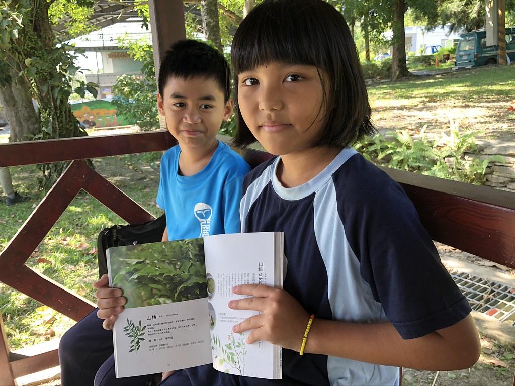 參與書籍紀錄繪畫的利嘉國小朱宇琁(右)與陳文政,展示他們在書中的貢獻。攝影:廖靜蕙