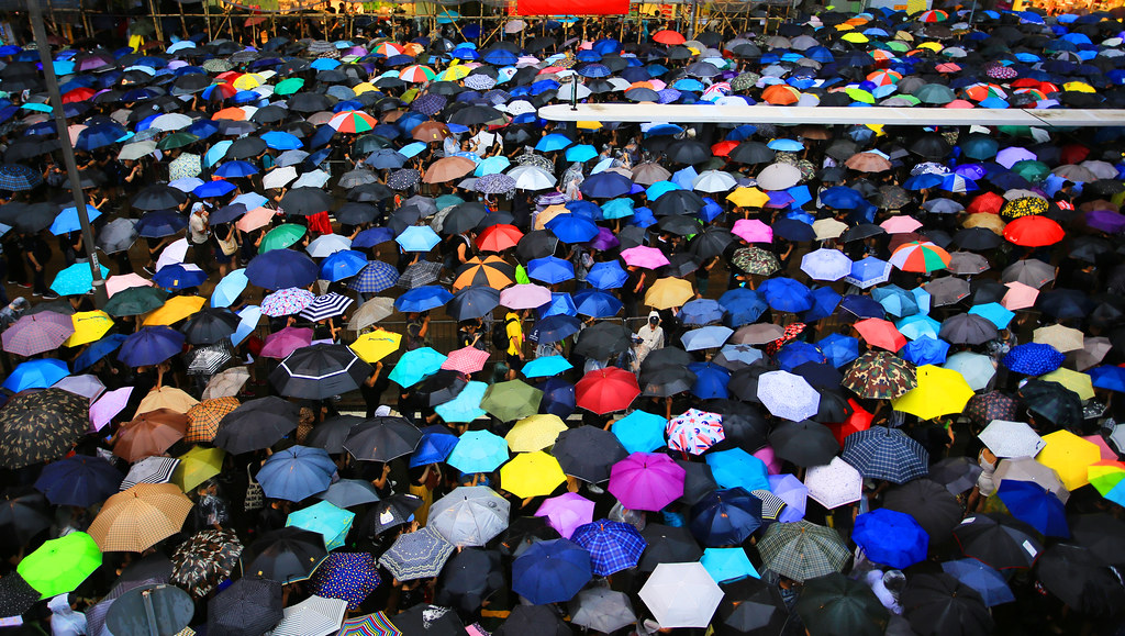 colourful open umbrellas seen from above in a crowded street