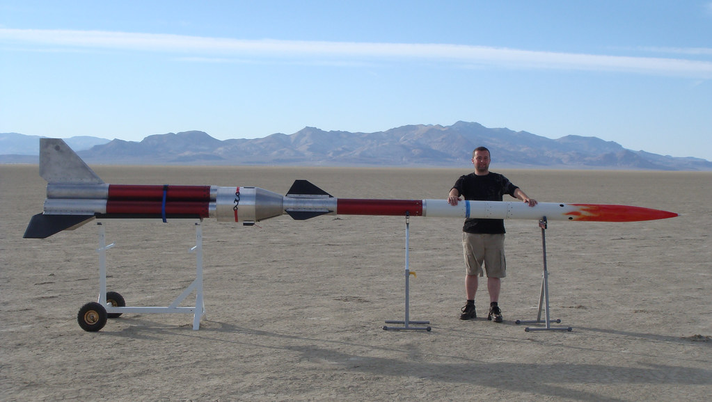 Dr Paul Shepherd standing in front of a rocket in a desert