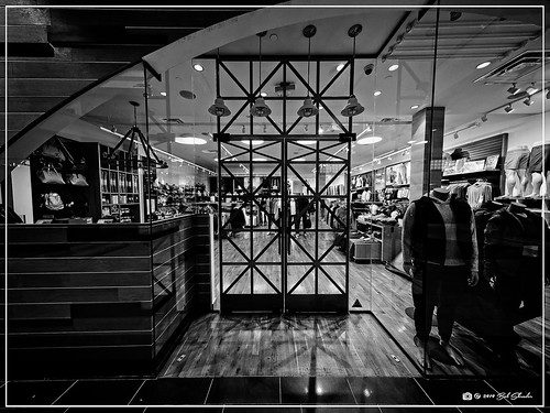 olympusem1markii olympusm8mmf18 8mm f18 1160sec 200iso raw microfourthirds mft m43 mirrorless northamerica unitedstatesofamerica america us unitedstates usa texas austin bartoncreeksquare traviscounty structure storefront building shoppingcenter glass clothing lights floor reflection shadow ceiling em1markii olympusomdem1ii omdem1markii primelens olympusmzuikodigital8mmf18fisheyepro fisheye interior wideshot dxo dxophotolab3elite dxoviewpoint3elite on1 photoraw2020 preset bwfilm bf7ilfordhp5400 blackandwhite bw blackwhite monochrome fauxfilm bwnegativefilm highcontrast monotone photoborder photoedge photoframe postprocessing style